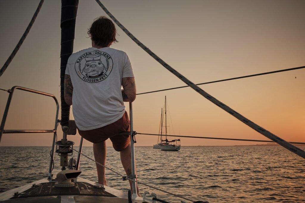 Lars vom Team Kapitän Ohlsens auf hoher See - Segeln im Klettershirt